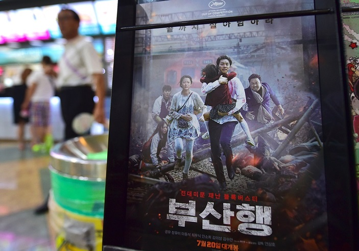 "A man walks past a poster of the first South Korean zombie blockbuster, entitled ""Train to Busan"", at a movie theater in Seoul on August 4, 2016.