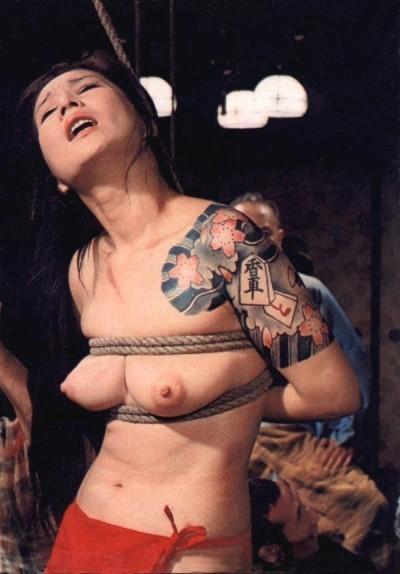 Naomi Tani, portraying tattooed Asian woman in bondage